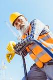 Gebaarde bouwvakker in weerspiegelend vest en bouwvakker die bij vangrail en het kijken leunen royalty-vrije stock afbeelding