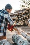Gebaarde brutale houthakker die de zagende boom van het plaidoverhemd met kettingzaag voor het werk aangaande zaagmolen dragen Ho royalty-vrije stock afbeeldingen