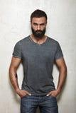 Gebaarde brutale kerel die lege grijze t-shirt dragen Royalty-vrije Stock Fotografie