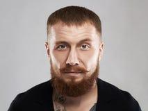 Gebaarde brutale misdadige mens met tatoegering Stock Afbeelding