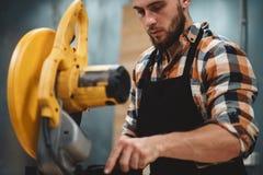 Gebaarde de dienstwerktuigkundige die aan elektro malende machine in benzinestation werken Het onderhouden van machines Werkschem royalty-vrije stock foto