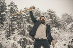 Gebaarde de greepbijl van de mensenhouthakker in sneeuw de winterbos, het kamperen royalty-vrije stock foto