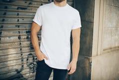 Gebaarde hipster die witte lege t-shirt dragen en Royalty-vrije Stock Afbeelding