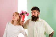 Gebaarde Hipster geeft het gebaar van de het meisjesverontschuldiging van boeketbloemen Man met baard apologyes vrouw Het boeketb royalty-vrije stock foto