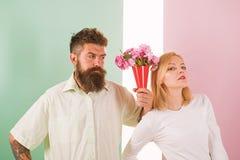 Gebaarde Hipster geeft het gebaar van de het meisjesverontschuldiging van boeketbloemen Man met baard apologyes vrouw Het boeketb stock foto