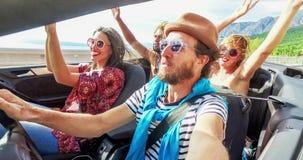 Gebaarde hipstermens die aan muziek met vrienden in convertibel luisteren, gesorteerd stock video