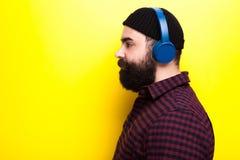 Gebaarde hipstermens die een zwarte hoed dragen en aan muziek luisteren royalty-vrije stock foto's