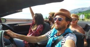 Gebaarde hipstermens die met hoed aan muziek met vrienden in convertibel luisteren stock video