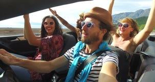 Gebaarde hipstermens die met hoed aan muziek met vrienden in convertibel luisteren stock footage