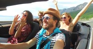 Gebaarde hipstermens met een hoed die met zijn vrienden in convertibel zingen stock footage