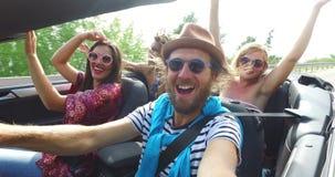 Gebaarde hipstermens met een hoed die zijn vrienden in convertibel drijven stock videobeelden