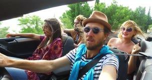 Gebaarde hipstermens met een hoed die zijn vrienden in convertibel drijven stock footage
