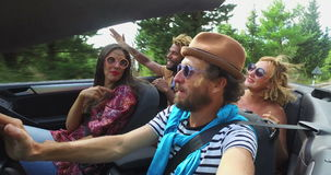 Gebaarde hipstermens met een hoed die zijn vrienden in convertibel drijven stock video