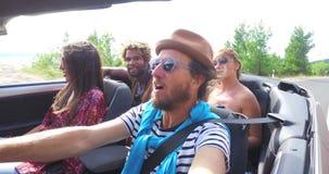 Gebaarde hipstermens met hoed die en met vrienden in convertibel drijven zingen stock footage