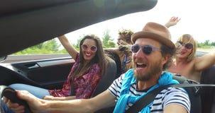 Gebaarde hipstermens met hoed die en met vrienden in convertibel drijven zingen stock video
