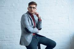 Gebaarde jonge mens die modieuze kostuumzitting dragen voor royalty-vrije stock fotografie