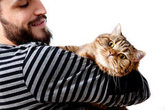 gebaarde jonge mens die zijn mooie kat op witte achtergrond omhelzen Royalty-vrije Stock Fotografie