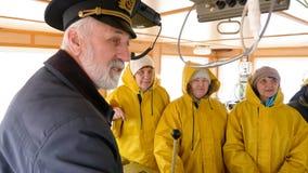 Gebaarde kapitein die met schipteam spreken in gele eenvormig in navigatiebureau Vrouwelijke schipbemanning en kapiteinsvergaderi stock footage