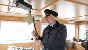 Gebaarde kapitein van schip het plaatsen radio op kapiteinsbrug De navigatieambtenaar leidt apparaten op navigatiepaneel en stock footage