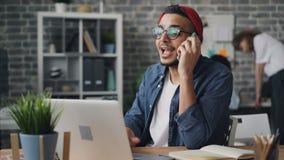 Gebaarde kerel die op mobiele telefoon spreken en laptop in creatief bureau met behulp van stock videobeelden