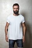 Gebaarde kerel die witte lege t-shirt dragen Stock Afbeeldingen