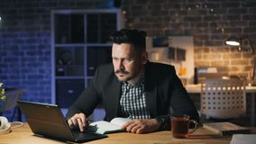 Gebaarde kerel gebruikend laptop bij nacht in bureau en makend nota's in notitieboekje bij bureau stock video