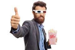 Gebaarde kerel met 3D glazen en popcorn die duim omhoog maken Stock Foto's