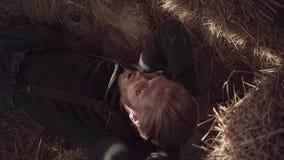 Gebaarde kerel met glazen die op het hooi in de schuur na het harde werk liggen Een bedrijfsmedewerker rust bij de onderbreking stock videobeelden