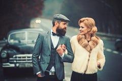 Gebaarde man en sexy vrouw in auto gebaarde mensenbestuurder op datum met sexy meisje in retro auto royalty-vrije stock afbeeldingen