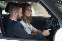 Gebaarde managerzitting met vrouw in auto en het tonen van cabine stock afbeelding
