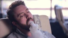 Gebaarde maniermens die elektronische sigaret roken stock video
