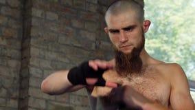 Gebaarde mannelijke bokser die zijn gewrichten verpakken alvorens te vechten stock footage