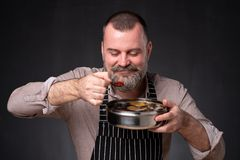Gebaarde mannelijke chef-kok die verschillende kruiden tonen die hij heeft gebruikt Geheim van heerlijk voedsel stock foto