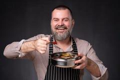 Gebaarde mannelijke chef-kok die verschillende kruiden tonen die hij heeft gebruikt Geheim van heerlijk voedsel royalty-vrije stock foto's
