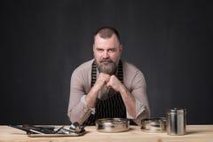 Gebaarde mannelijke chef-kok die verschillende kruiden tonen die hij heeft gebruikt Geheim van heerlijk voedsel royalty-vrije stock afbeelding