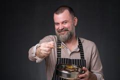Gebaarde mannelijke chef-kok die verschillende kruiden tonen die hij heeft gebruikt Geheim van heerlijk voedsel stock afbeeldingen