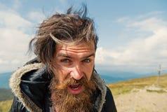 Gebaarde mens, brutale Kaukasische hipster met snor op winderige berg stock foto's