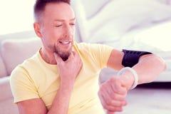 Gebaarde mens die binnen voor sport gaan die zijn smartwatch bekijken die calorieën controleren stock foto's