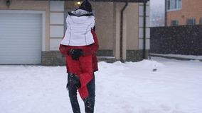 Gebaarde mens die de winterjasjes dragen die rond zijn meisje, beide het lachen spinnen Het gelukkige paar heeft een pret in de w stock footage