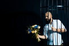 Gebaarde mens die een boeket met bloemen standhouden De brutale man in de kooi over zwarte achtergrond Royalty-vrije Stock Afbeeldingen