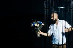 Gebaarde mens die een boeket met bloemen standhouden De brutale man in de kooi over zwarte achtergrond Stock Fotografie