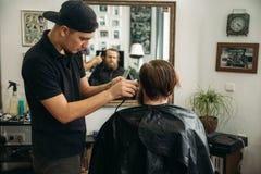 Gebaarde mens die een kapsel met een haarclippers hebben stock afbeelding