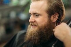 Gebaarde mens die een kapsel met een haarclippers hebben royalty-vrije stock fotografie