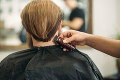 Gebaarde mens die een kapsel met een haarclippers hebben stock afbeeldingen