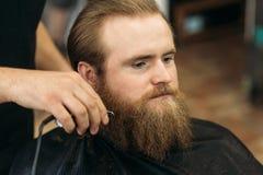 Gebaarde mens die een kapsel met een haarclippers hebben royalty-vrije stock foto's
