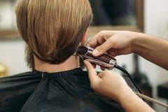 Gebaarde mens die een kapsel met een haarclippers hebben stock foto