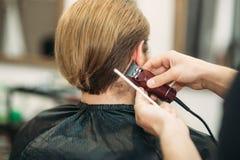 Gebaarde mens die een kapsel met een haarclippers hebben stock foto's