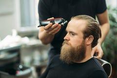 Gebaarde mens die een kapsel met een haarclippers hebben royalty-vrije stock afbeeldingen