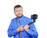 Gebaarde mens die die een selfiestok gebruiken in studio wordt geschoten Geïsoleerdj op witte achtergrond stock fotografie