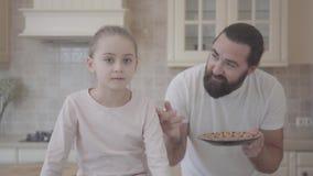 Gebaarde mens die emotioneel verhaal vertellen aan zijn kleine dochter die, actief achter haar terug met in hand plaat gesticuler stock video